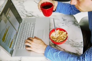 a man working at home while eating breakfast